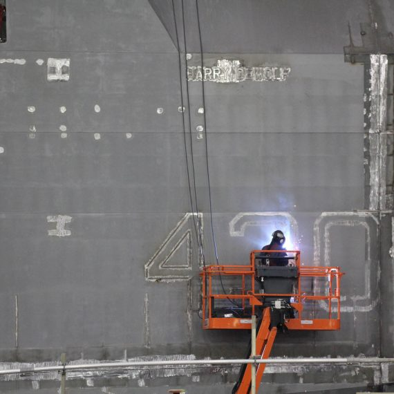 The name and hull number of the future HMCS Harry DeWolf are marked on the ships bow before the mega-block is painted.